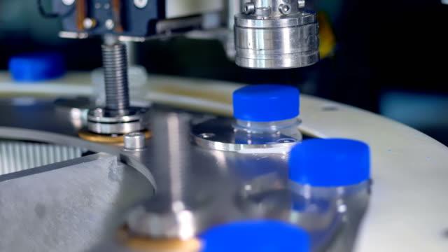 Macro view on milk bottles receiving blue caps. video