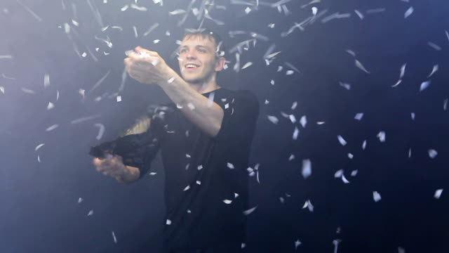 Magician shows focus with fan and white confetti on dark background video