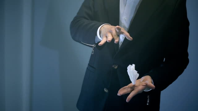 magician shows trick with flying white napkin on black background. video