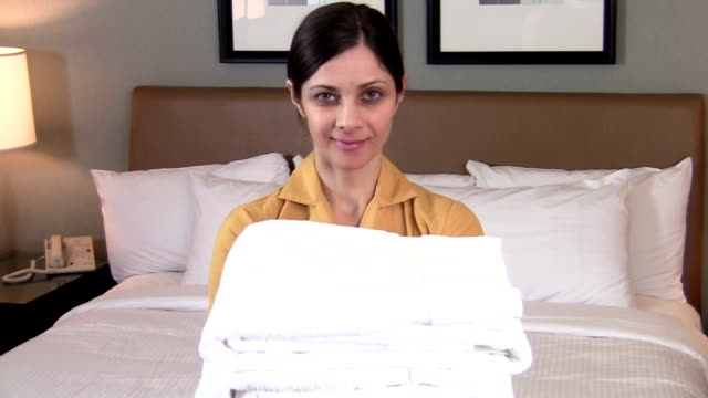 Maid portrait holding towels - HD video