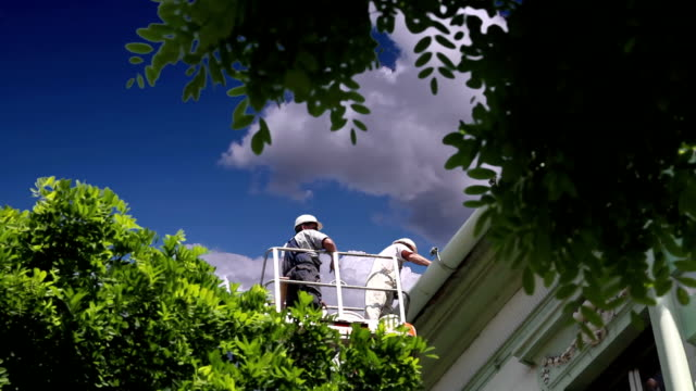 Maintenance Workers in a Bucket Repairing the Roof video