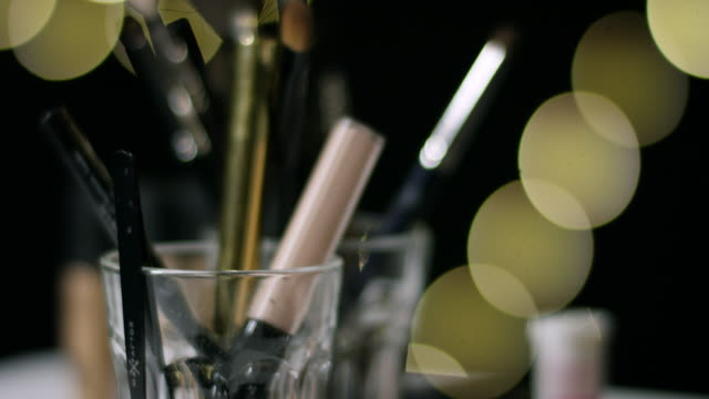 Make up objects and hand putting back pen in a glass. video