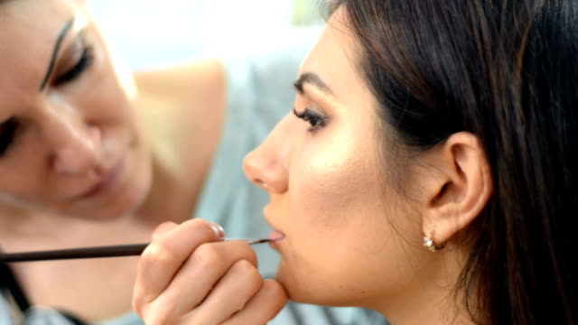 Makeup artist apply makeup to an attractive young woman video