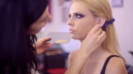 Make-up artist applying make up with a brush on model's face video