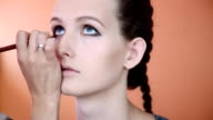 Makeup artist applying professional make up on the face of the beautiful young female model. Orange background video