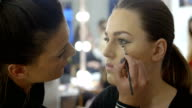 Makeup artist making makeup for young woman video