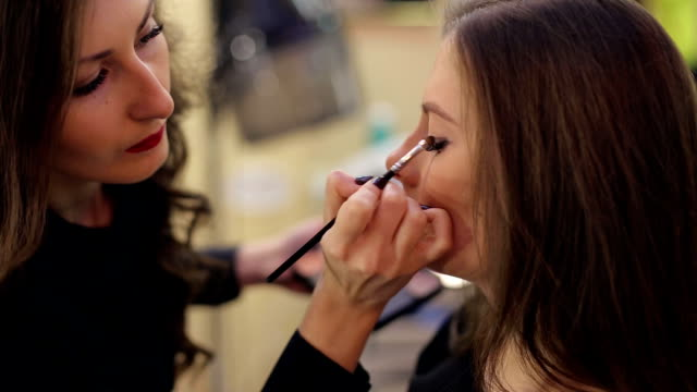 Makeup artist making professional makeup for woman video