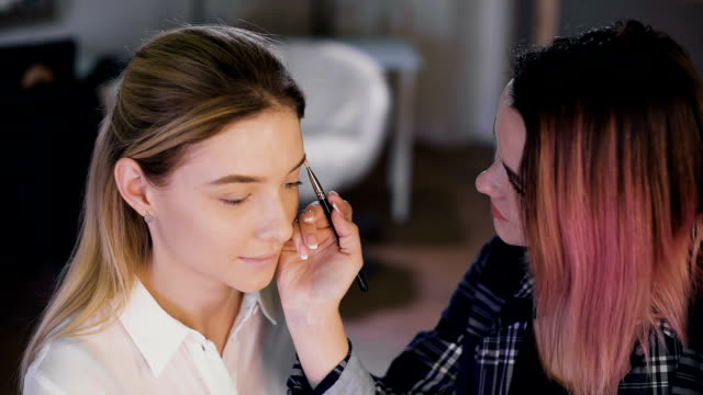 Make-up artist work on her friend. Real people video