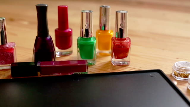Make-up  colorful cosmetic palette, lipstick, brushes and nail laquer bottles video