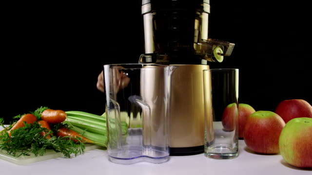 Making freshly squeeze juice from carrots and celery  using cold press juicer video