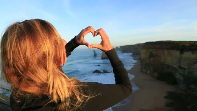 Making heart shape finger frame to the Twelve Apostles, Australia video