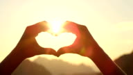 CLOSE UP: Making heart with hands against setting sun and golden evening sky video