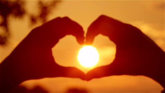 CLOSE UP: Making heart with hands around the sun video