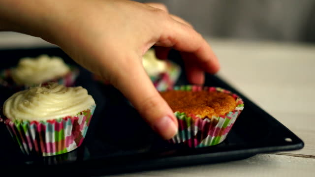 Making muffins. Cooking cupcakes. Hand take away cake from baking tray video