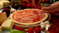 Making pizza-adding oregano i video