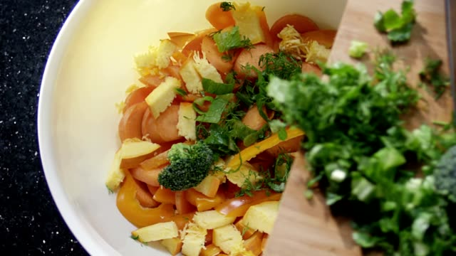 Making salad with fresh herbs, broccoli, pepper,pumpkin and carrots. Shot on RED EPIC Cinema Camera in slow motion. video