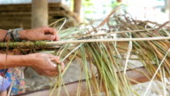 Making thatch roof with grass Dolly Shot video