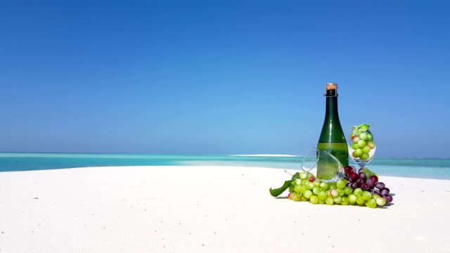Maldives beautiful beach background white sandy tropical paradise island with blue sky sea water ocean 4k champagne bottle glass grapes video