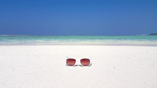 Maldives beautiful beach background white sandy tropical paradise island with blue sky sea water ocean 4k sunglasses video