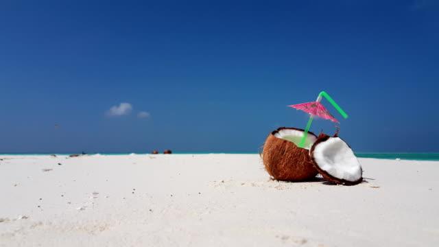 Maldives beautiful beach background white sandy tropical paradise island with blue sky sea water ocean 4k coconut milk juice drink video