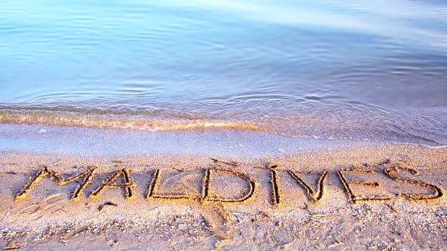 Maldives the inscription on the sand. video