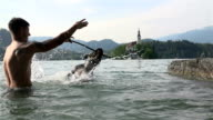 SLOW MOV: Male and dog playing with stick in lake video
