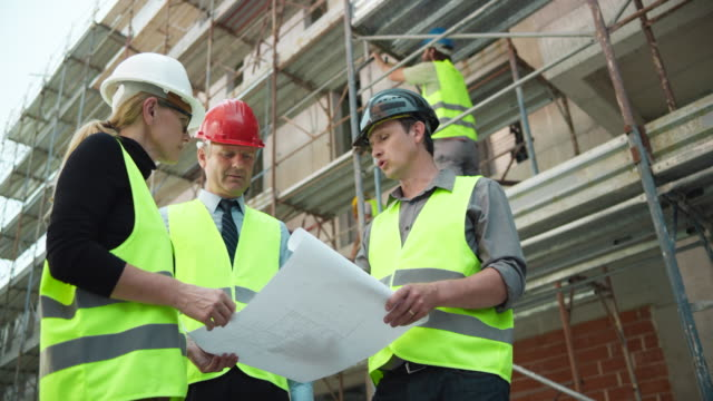 Male and female architect presenting plan details to the male investor at the construction site video