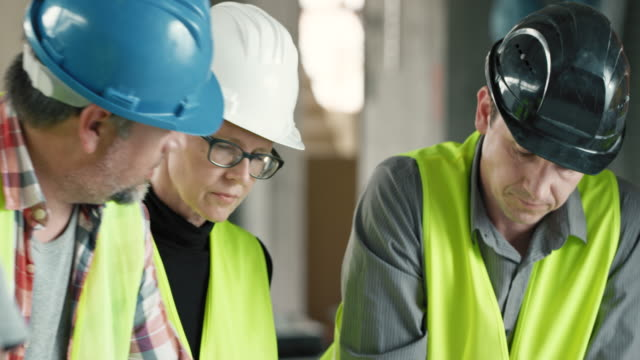 TU male and female architect talking to the site manager at the construction site and going over the plan details video