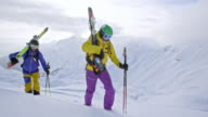 Male and female backcountry skier reaching mountain top video