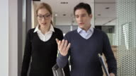 DS Male and female business coworker walking and talking in hallway video