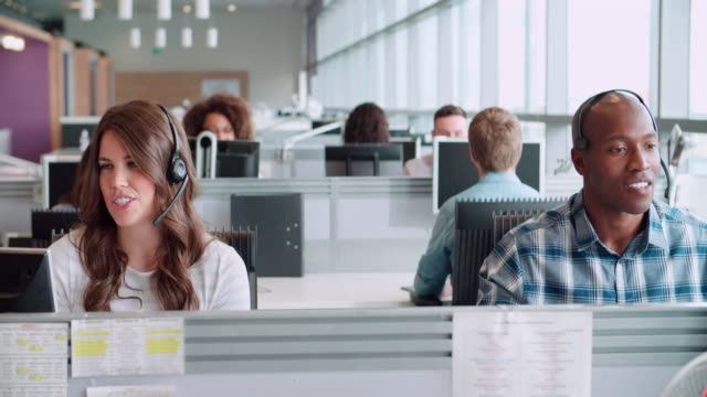 Male and female call centre workers wearing headsets video