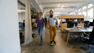 Male and female colleagues skateboarding video