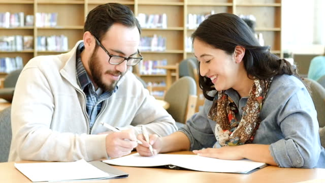 Male and female Hispanic adult college students smiling as they study together in library video
