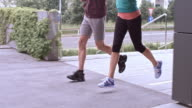 SLO MO Male and female legs running in city video