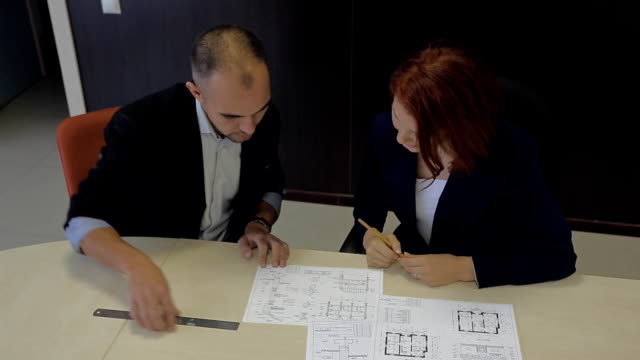male and female professionals working together on a blueprint house schemes video