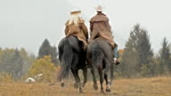 SLO MO DS Male and female rancher riding galloping horses video