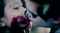 Male and female teenagers with scary makeup on faces kissing video