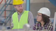 Male and female worker in the factory working and talking video