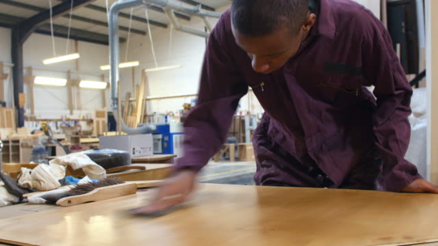 Male apprentice in carpentry workshop polishing piece of wood.Shot on Sony FS700 at a frame rate of 25fps video