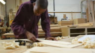 Male apprentice sanding piece of wood in carpentry workshop.Shot on Sony FS700 at a frame rate of 25fps video