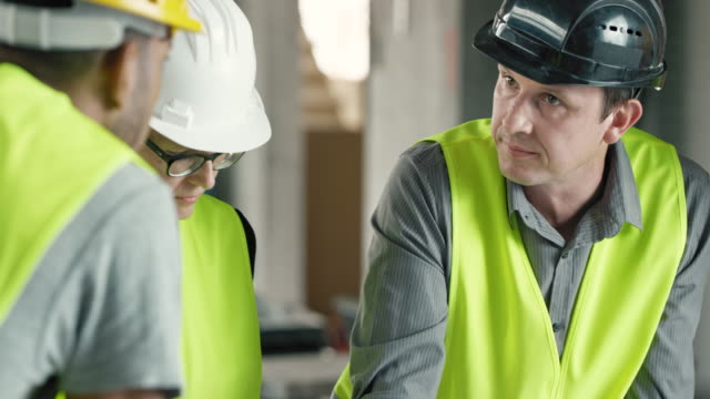 Male architect talking to his female colleague and foremen at the construction site, going over the plans on the table video