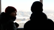 Male architects make panoramas with compact camera from a height in winter, discussing something video