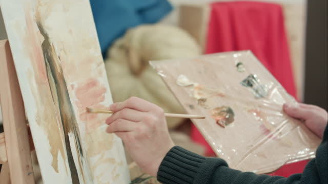 Male artist hands applying brush strokes on canvas and holding palette video