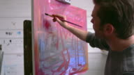 Male Artist Working On Painting In Studio Shot On R3D video