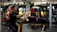 male athlete the coach helps young attractive woman in the gym to engage in the development of the chest muscles, helping to raise the dumbbells and shows how to do it right video