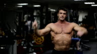 Male athlete with an athletic physique, posing in gym video