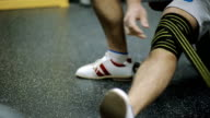 male athletes aged rewinds his knee on the leg hair sport athletic bandage black with yellow stripes, for Security, to load on the joint video