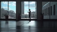 Male athletic standing near a window in a dark hallway and gaining a message on the phone video