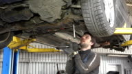 Male auto mechanic with spanner working under car in garage video