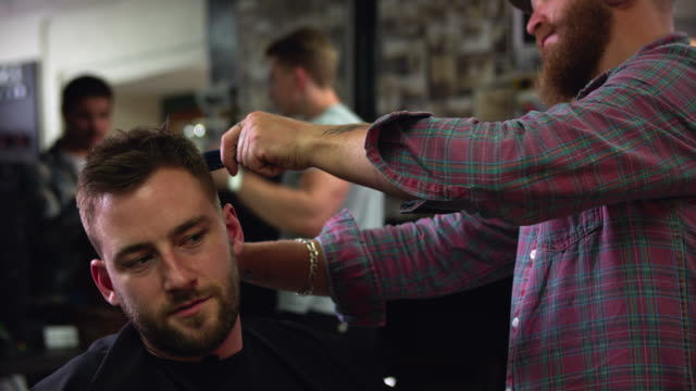 Male Barber Giving Client Haircut In Shop video